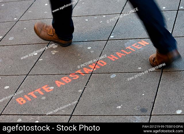 """19 December 2020, Lower Saxony, Hanover: The words """"""""Please keep your distance"""""""" can be read on the floor outside the entrance to a pharmacy in the city centre"""