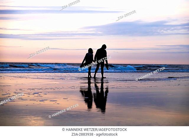 A couple walking hand in hand during sunset at the beach of Scheveningen, The Hague, The Netherlands, Europe