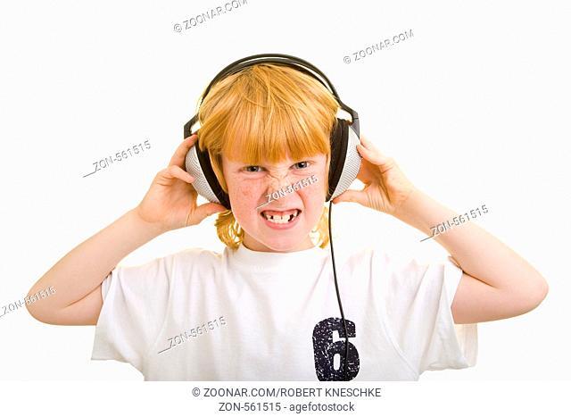 Junge hört Musik mit Kopfhörern und schaut dabei grimmig