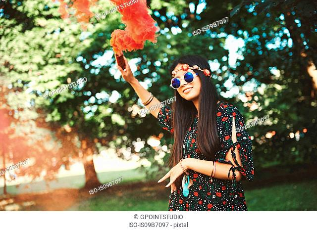 Young boho woman holding up red smoke flare at festival