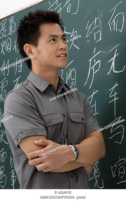 man standing in front of Chinese characters written on chalk board