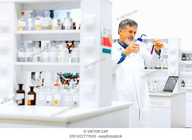 Senior male researcher carrying out scientific research in a lab (shallow DOF color toned image)