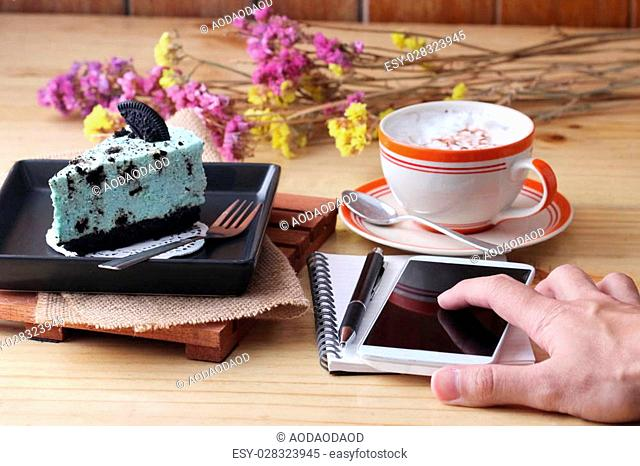 notebook pen and coffee cup with cake and cookie, cafe
