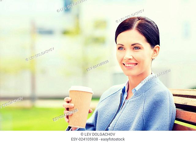 drinks, leisure and people concept - smiling woman drinking coffee outdoors
