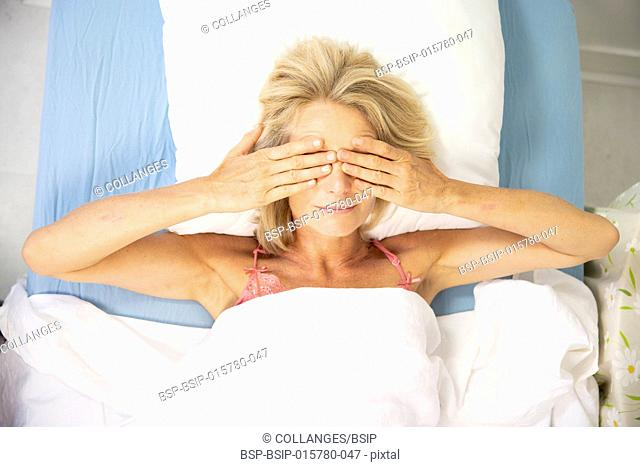 Woman rubbing her eyes in the morning