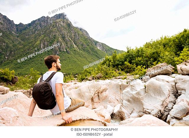 Man sitting on rocks looking away, Accursed mountains, Theth, Shkoder, Albania, Europe