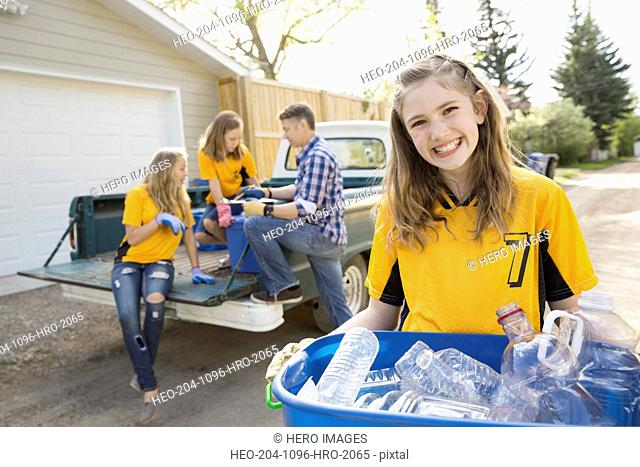 Portrait of smiling girl holding recycling bin