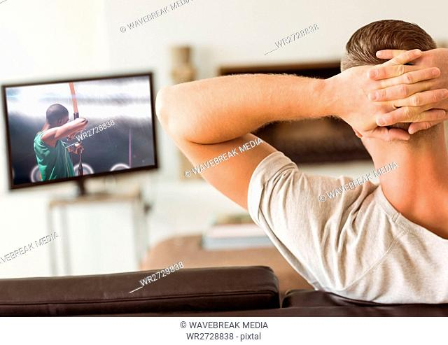 Rear view of man watching television in living room