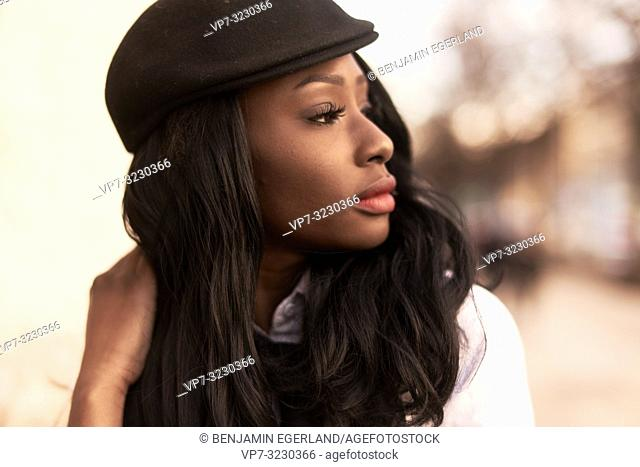 headshot of stylish woman looking aside, retro look, African Angolan descent, in Munich, Germany