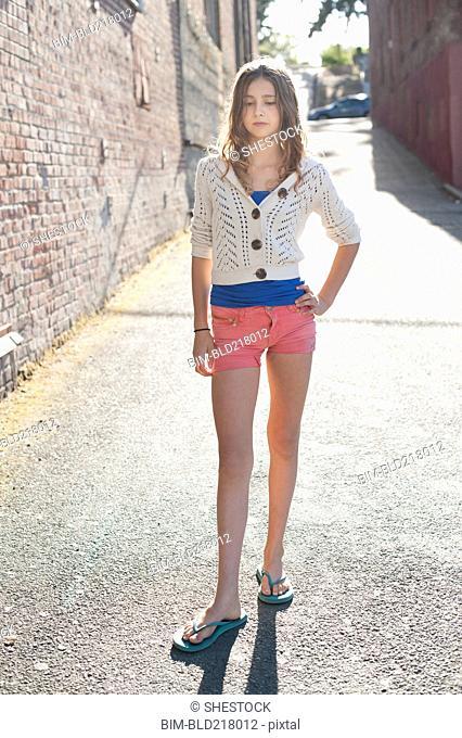 Girl standing in city alleyway
