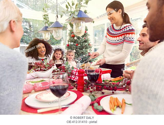 Woman serving turkey at Christmas dinner table