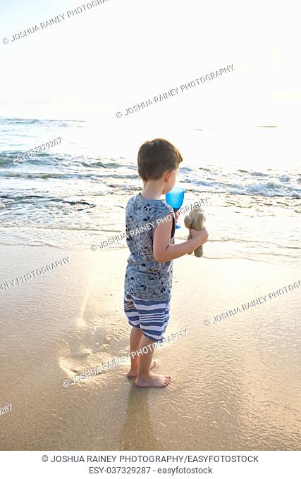 Child at the beach with feet in the water of the Pacific Ocean at sunrise in Oahu Hawaii