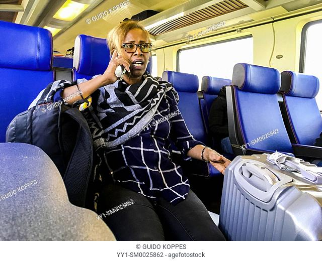 Amsterdam, Netherlands. International, female traveler, commuting the last stretch of her journey by Direct Intercity Train