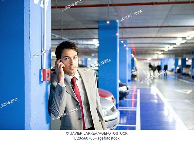 Businessman with mobile phone. Parking lot