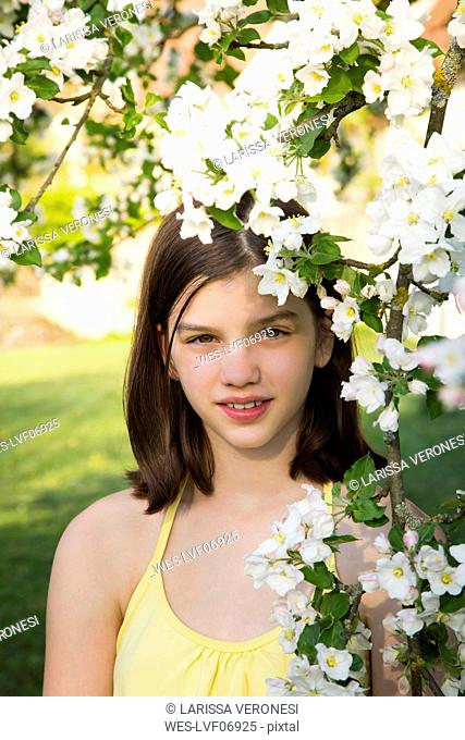 Portrait of girl with twig of blossoming apple tree