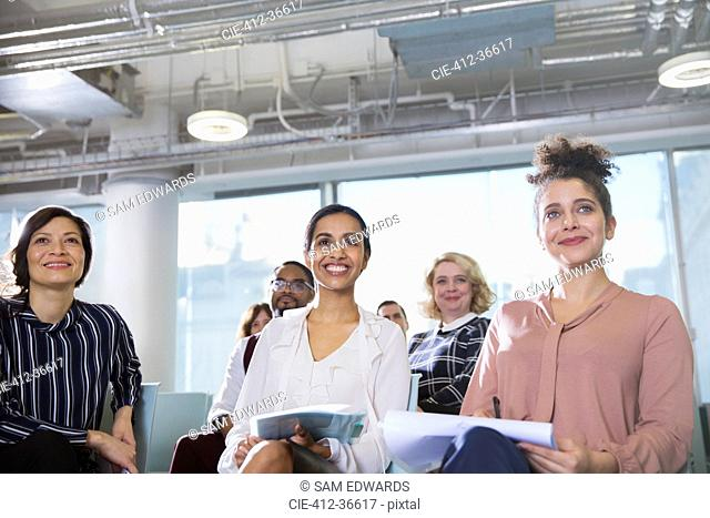 Smiling, attentive businesswoman listening in conference audience