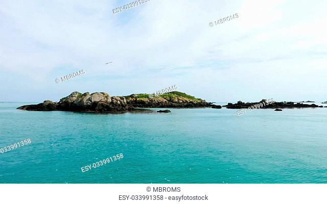Small rocky islands on the horizon in the archipelago of Iles de Chausey. Brittany, France