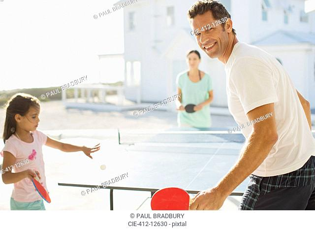 Family playing table tennis outside house