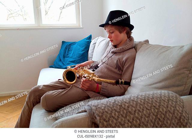 Boy practising saxophone on sofa