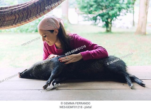 Peru, Woman cuddling domesticated peccary