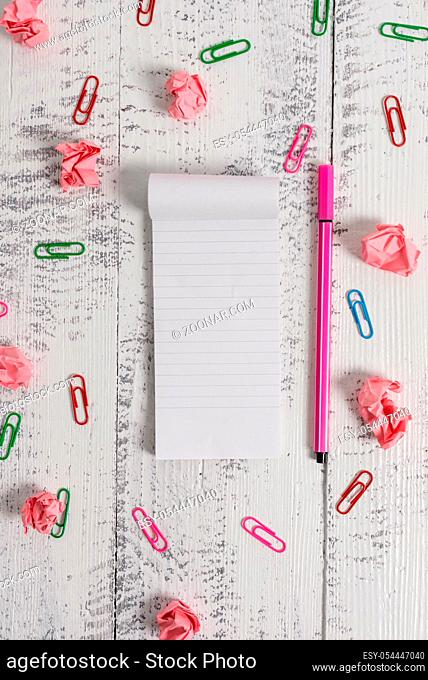 Stripped notepad clips paper balls pen lying wooden vintage background