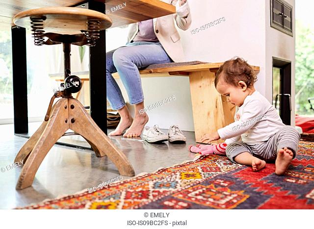 Mother working at kitchen table, whilst baby girl plays on floor. low section