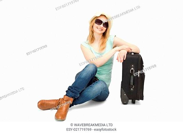 Woman sitting next to a suitcase