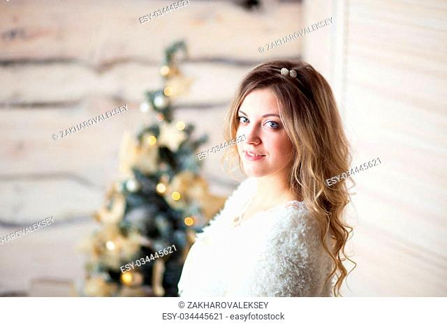 girl near the decorated Christmas tree in beautiful light the interior in a festive morning