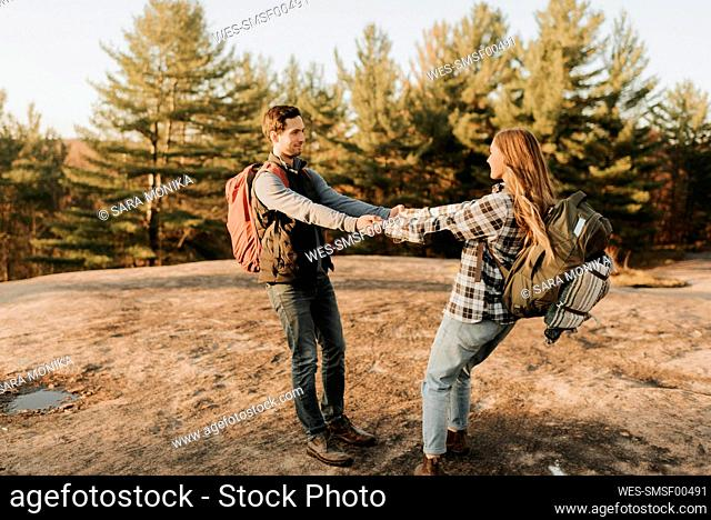 Young couple holding hands during autumn hike