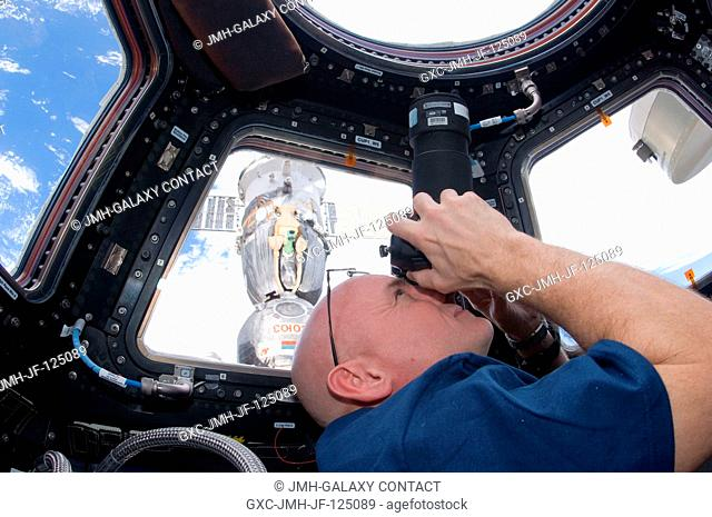 NASA astronaut Scott Kelly, Expedition 25 flight engineer, uses a still camera to photograph the topography of a point on Earth from a window in the Cupola of...