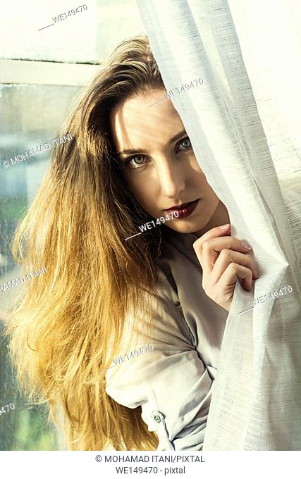 Beautiful young woman hiding behind the blinds
