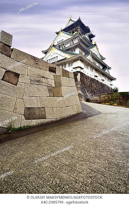 Osaka Castle, Osakajo and its stone fortification wall, low angle view, beautiful misty morning sunrise scenery. Osaka, Japan 2017