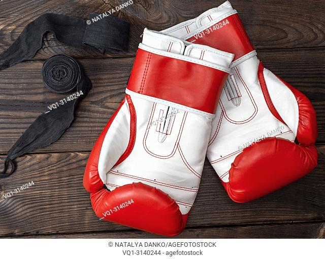 pair of red leather boxing gloves and elastic black bandage on a brown wooden background, top view