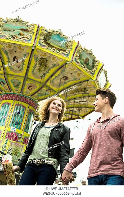 Teenage couple at fun fair with chairoplane in the background