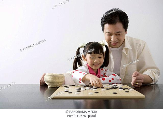 Father and daughter playing I-go