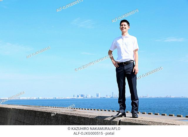 Portrait of young Japanese man by the sea