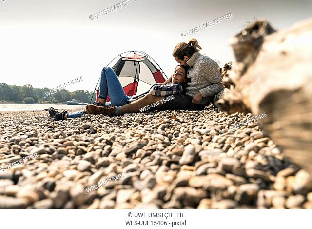 Happy young couple relaxing at a tent at the riverside