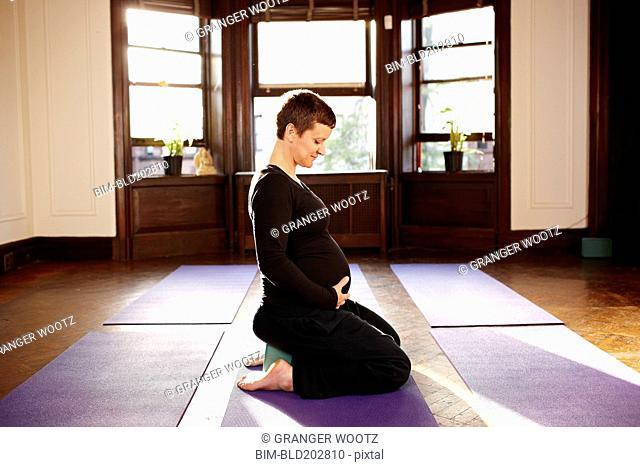 Pregnant woman sitting on yoga mat