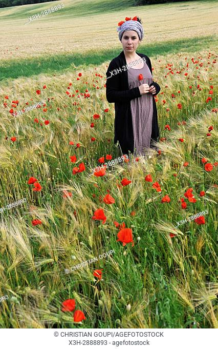young woman in a cereal field dotted with poppies, France, Europe