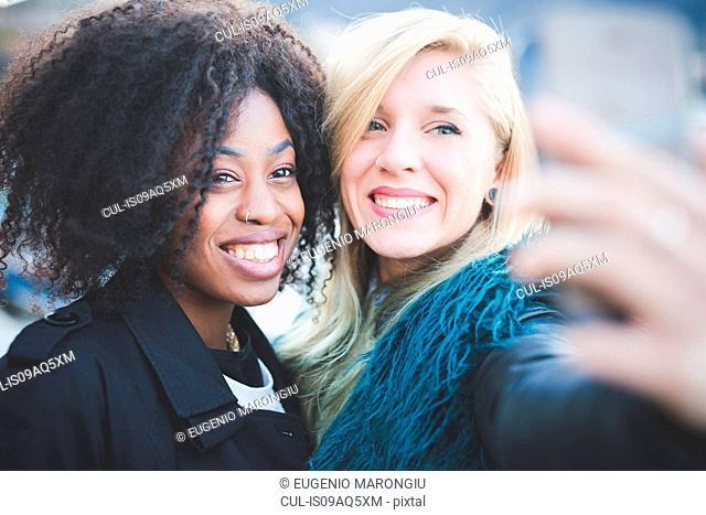 Two young women posing for smartphone selfie, Lake Como, Como, Italy