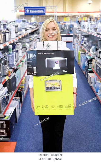 Young woman with boxes in shop, smiling, portrait