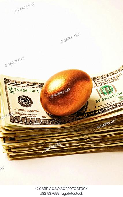 Golden egg sitting on top on a stack of American money