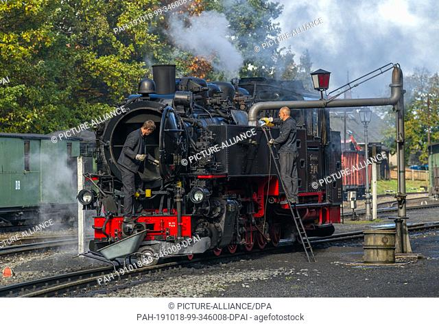 10 October 2019, Saxony, Bertsdorf: At the station, water is filled into a locomotive of the Zittau narrow-gauge railway