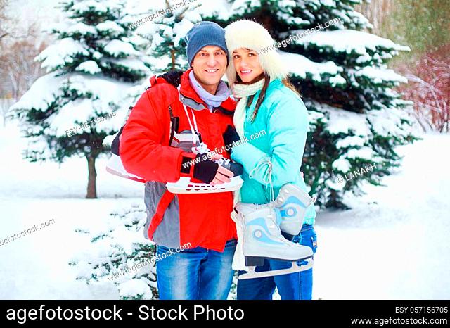 happy young couple going ice-skating outdoor in wintertime