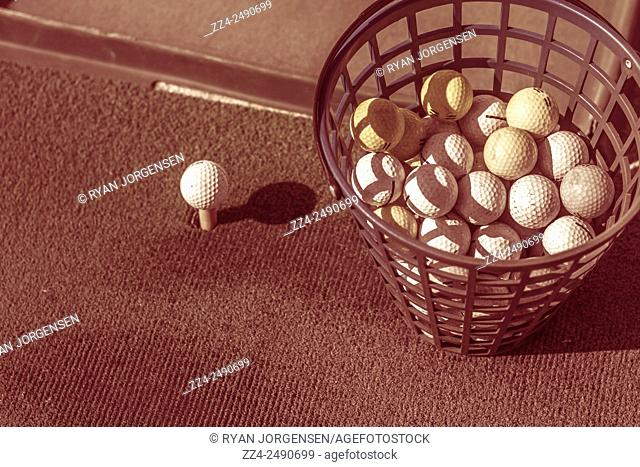 Old toned image of a bucket of golf balls next to practise tee a driving range. Vintage sport objects