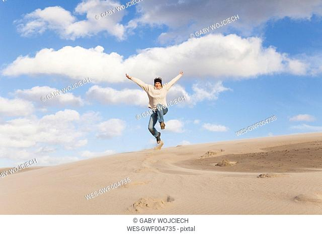 Enthusiastic mature woman jumping over sand dune
