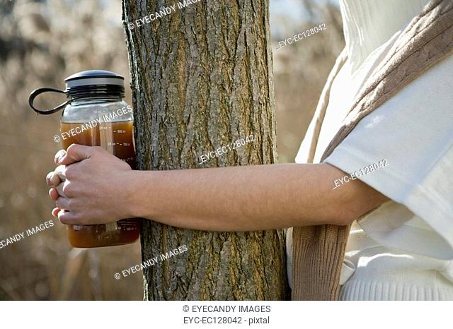 Hands holding a tea kettle around tree trunk