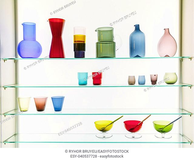 Assorted Different Sizes And Shapes Of Colorful Glassware On Shelves. Vases, Pitchers, Jugs, Glasses On White Background