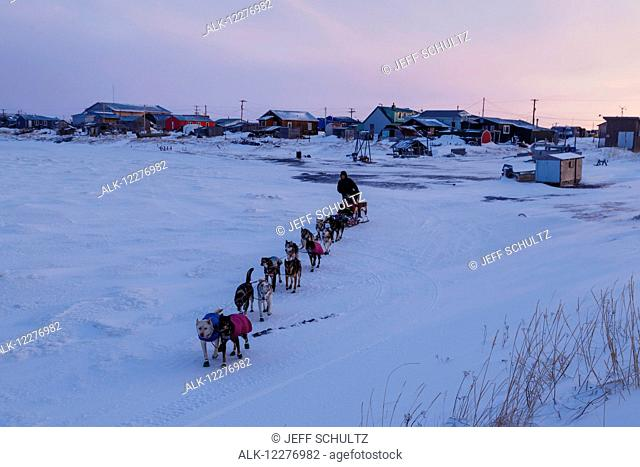 Aaron Burmeister runs on the slough leaving the Unalakleet checkpoint at sunset during Iditarod 2015