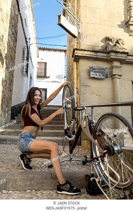 Spain, Baeza, smiling young woman repairing her bicycle